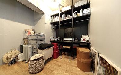 机の上にハンガーポールや棚が造り付けられた書斎兼ウォークインクローゼット。一見ただの書斎にしか見えないほど整然としているが、アルミ製のキャンプ用品の収納ケース(机の上部、棚の最上段)やインテリアショップで見つけたデザイン性の高い丸箱(写真右)、アンティークの大型旅行鞄やコンテナ(写真左)に季節外の物を全て収納(写真撮影/飯田照明)