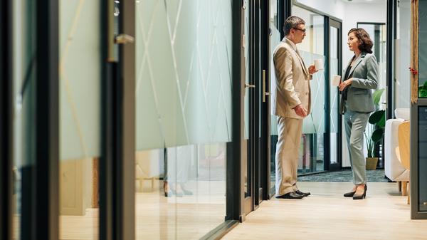 オフィスの廊下で立ち話する男女