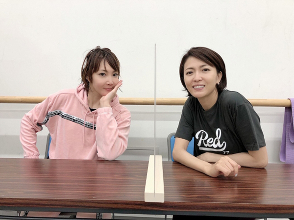 柚希と、新キャストで同役を演じる安蘭けい(右)。机には仕切りが設置されている (C)ホリプロ