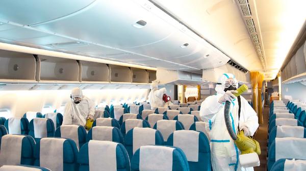 飛行機内を消毒する人