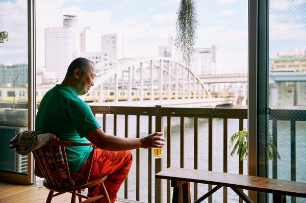 窓のそばでビールの入ったグラスを持つ邦夫さん