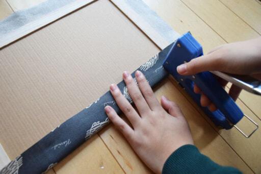 コルクボードに布を巻き、棚板に蝶番をつけて扉をDIY