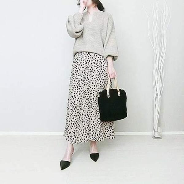 ベージュのキーネックニットにダルメシアン柄ロングスカートを合わせ、黒のパンプスと黒のボアハンドバッグをコーディネート