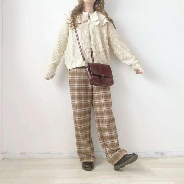 白の大きめの襟ディテールのブラウスにケーブル編みカーデを羽織りブラウンのチェック柄ストレートパンツを合わせ黒の靴とブラウンのショルダーバッグをコーディネート