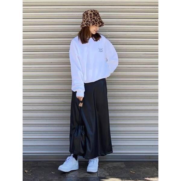 白のクルーネックスウェットに黒のレザースカートを合わせ、白のスニーカーとショルダーバッグ、ブラウンのバケットハットをコーディネート