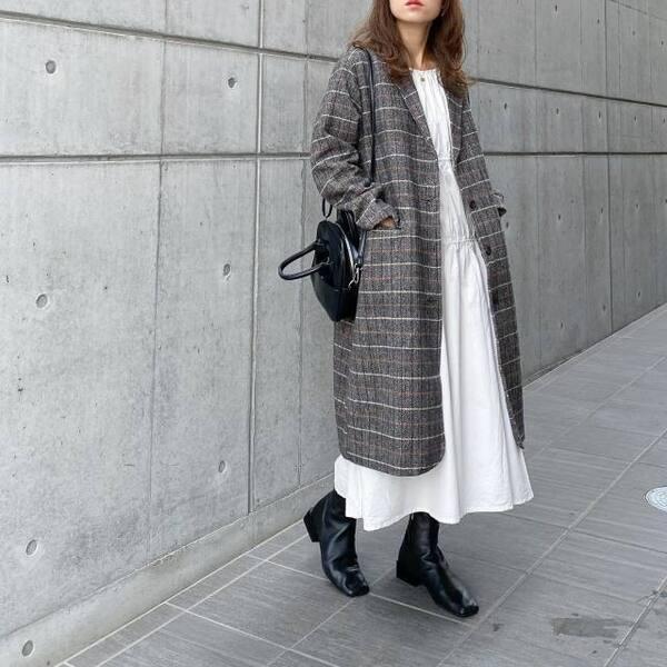 白のフレアワンピにチェック柄のチェスターコートを羽織り、黒のスクエアブーツとショルダーバッグをコーディネート