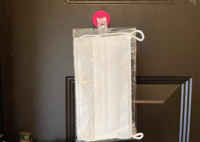 クリップ付きマグネットで玄関ドアにマスクを張り付けている