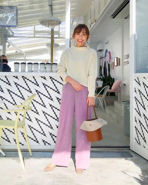 白のニットにピンクのワイドパンツを合わせ、ベージュパンプスとキャメル色バケツバッグをコーディネート