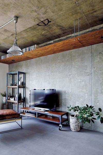 上部に棚を設置したモルタル壁のリビング