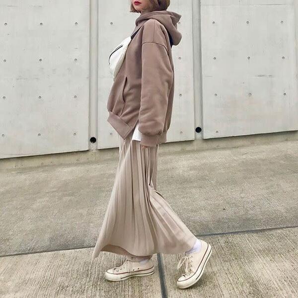 モカカラーのフーディにベージュのプリーツスカートを合わせ、白のプリーツバッグ、白のスニーカーをコーディネート