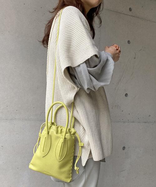 カプリシュレマージュのイエローショルダーバッグを持っている女性の写真