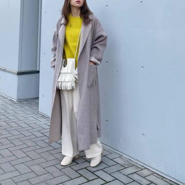 黄色のクルーネックニットに白のワイドパンツを合わせグレージュのチェスターコートを羽織り、白のフリンジショルダーを掛け、白のスクエアブーツをコーディネート