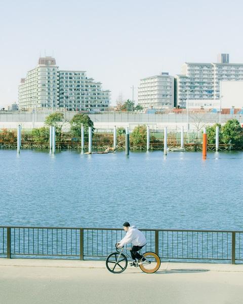川沿いで自転車に乗る