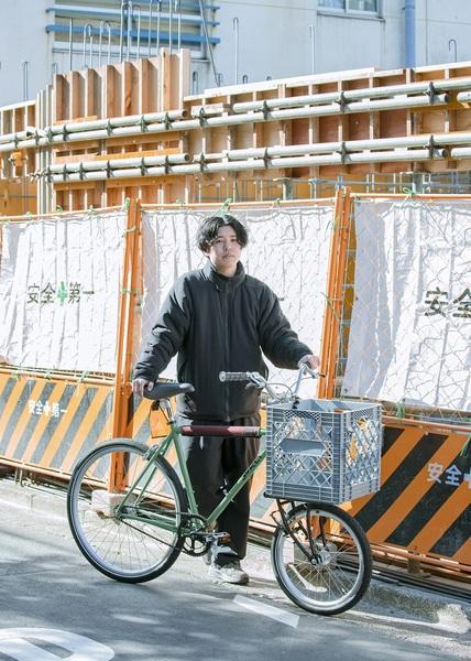 自転車の横に立つ藤本さん