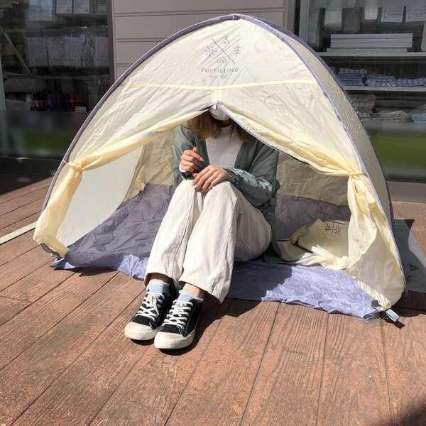 スリーコインズのカーテン付きPOPUPテントに女性が座っている写真