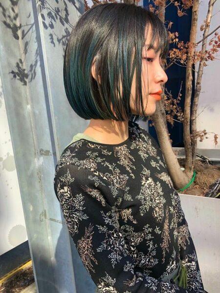 女性の黒髪ボブ×グリーン系インナーカラー