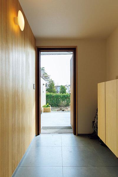 木製フェンスの延長線上にある玄関の壁は板張りに