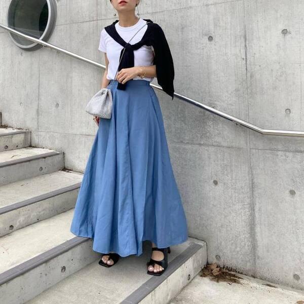 ユニクロのクルーネックTにブルーロングフレアスカートを着ている女性の写真
