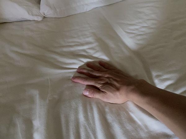 北見ハッカ油配合 ひんやりシャツシャワーをスプレーしたシーツを触る手