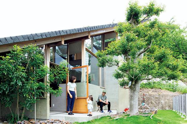 大屋根が印象的な家と呉屋さん親子