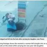 赤ちゃんを抱いてスマホ通話の女性、蓋のないマンホールに転落(印)<動画あり>